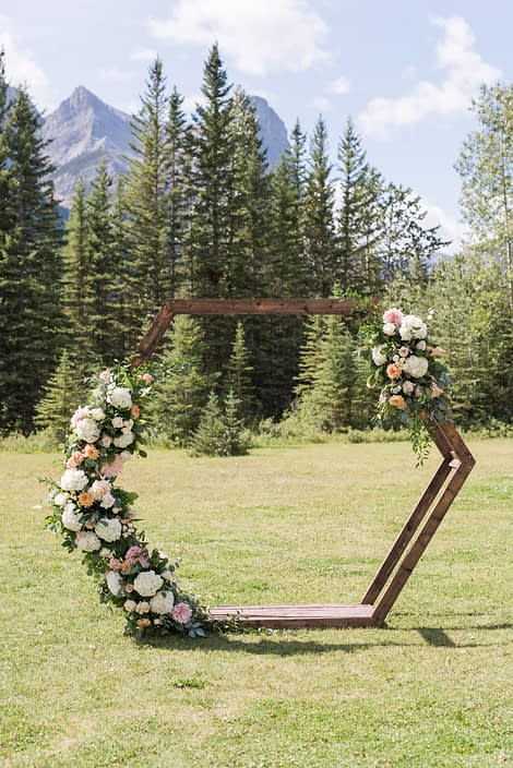 Wooden hexagon archway for Amy and Kerry's Pink and Blue Canmore Wedding set in the Rocky Mountains. It is decorated with fresh floral arrangements featuring white o'hara garden roses, white hydrangea, peach chrysanthemums, quicksand roses, astilbe, salal and eucalyptus.