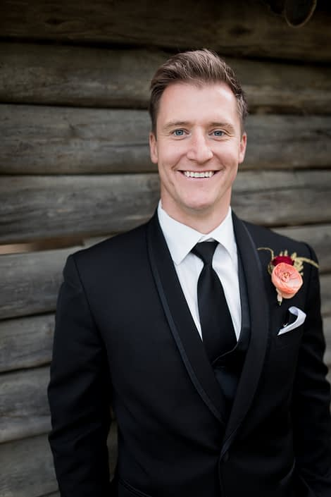 Groom in black tux with salmon ranunculus and burgundy spray rose boutonniere