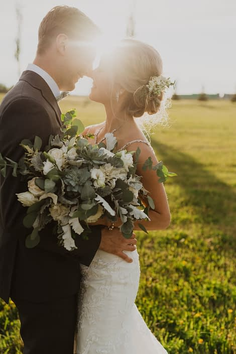 Bride and groom in the sunshine; bride hair flowers designed with white spray roses, astilbe, lisianthus and grey toned greenery; bridal bouquet featuring white Playa Blanca roses, white lisianthus, white astilbe, Blue Star succulents, dusty miller and eucalyptus.