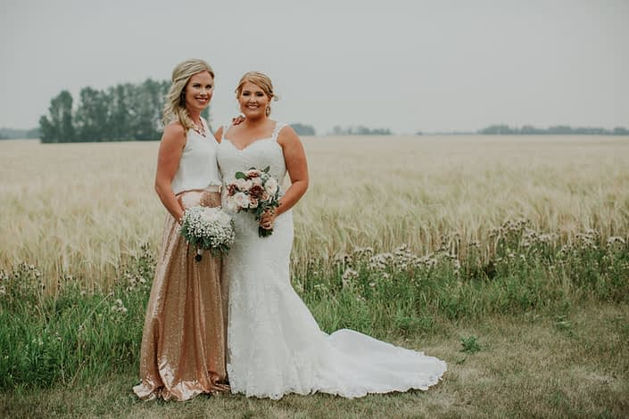 Bride with bridesmaid in a summer wheat field wearing a rose gold sequin bridesmaid dress holding a bouquet of babies breath and garden roses