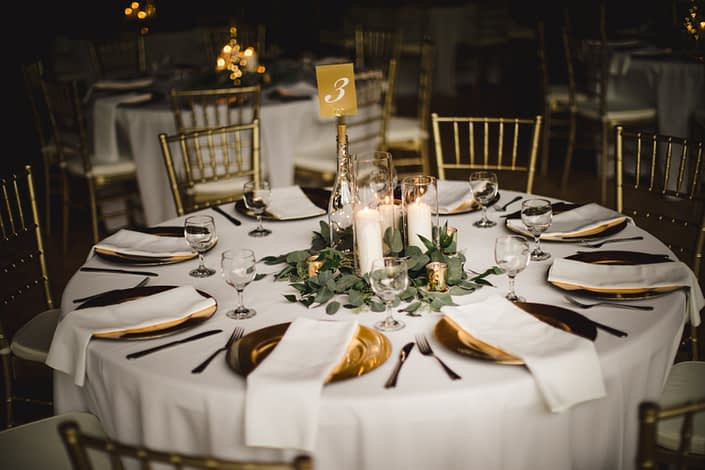 Boho Glam centrepiees created with fresh loose greenery around the base of white pillar candles with gold accents.
