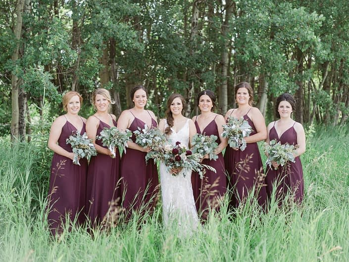 Burgundy country chic wedding bride and bridesmaids holding bouquets; bridal bouquet designed with dahlias, quicksand roses, lisianthus, astrantia, astilbe and various types of greenery including eucalyptus, dusty miller and olive branches; bridesmaids carrying greenery bouquets.