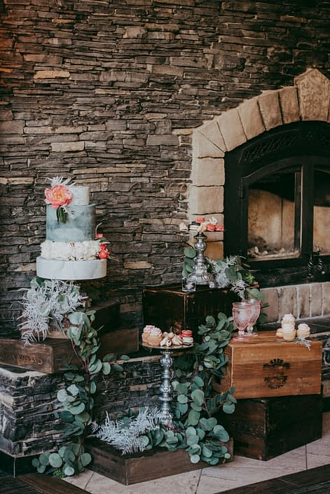 Dessert area on the hearth of the stone fireplace at Canyon Ski Resort. Cake, cupcakes and macarons all arranged and decorated with coral charm peonies, white peonies and eucalyptus.