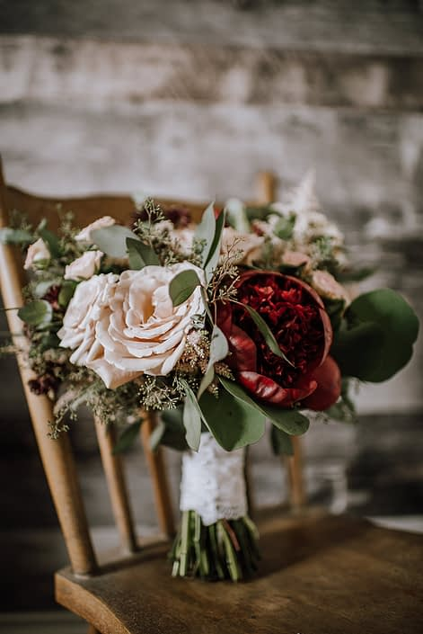 Rustic red and blush bridal bouquet designed with quicksand roses, red charm peony, burgundy astrantia, pale pink astilbe, and blush spray roses finished with eucalyptus greenery and a blush satin with lace overlay handle wrap.