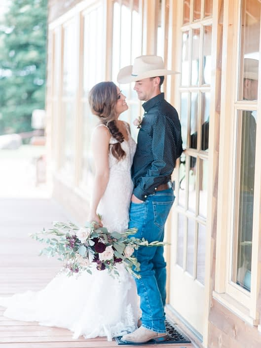 Bride and cowboy groom with burgundy and blush country chic bridal bouquet.