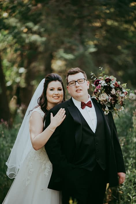 Bride and groom with rustic burgundy and dusty rose bridal bouquet featuring roses, dahlias and ranunculus