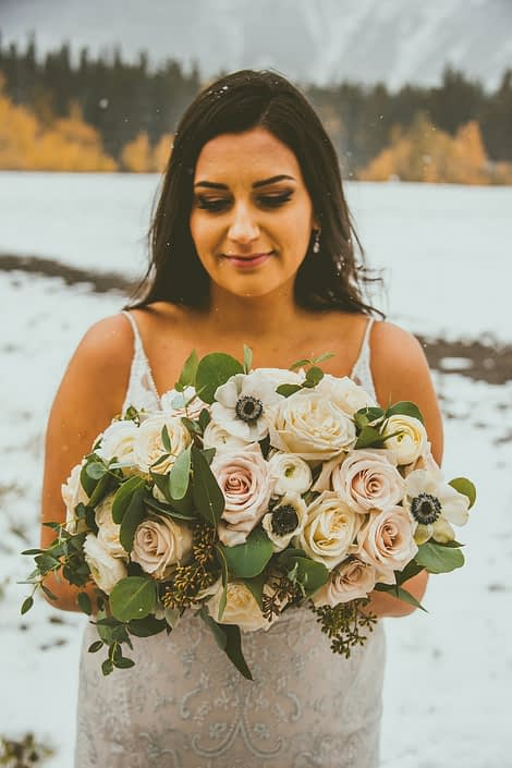 Our bride Meagan holding a gorgeous hand-tied bouquet made of panda anemones, white ranunculus, ivory playa blanca roses, blush pink quicksand roses, and eucalyptus greenery.