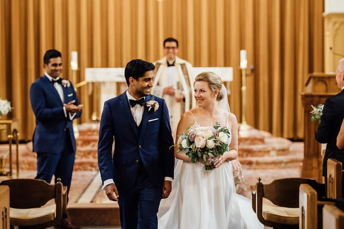 Bride and groom walking up aisle; groom wearing boutonniere; bride holding blush bouquet made with quicksand roses, white o'hara garden roses, white ranunculus, light pink astilbe and a variety of eucalyptus greenery.
