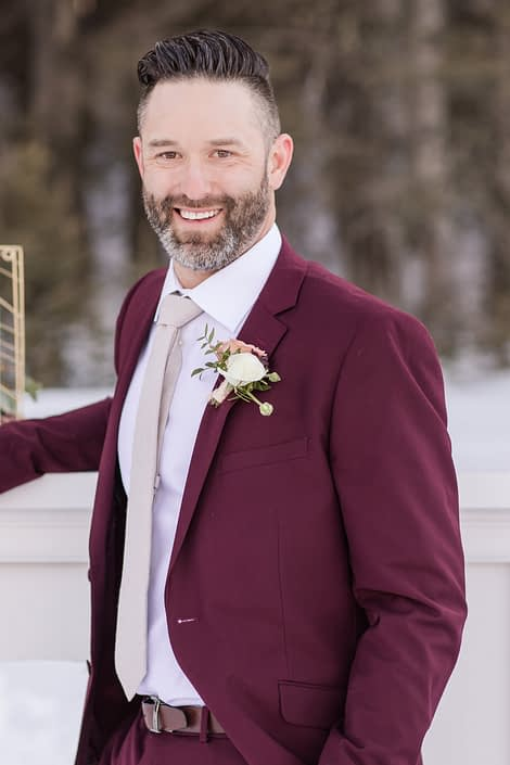 winter groom in a burgundy suit with ivory ranunculus boutonierre