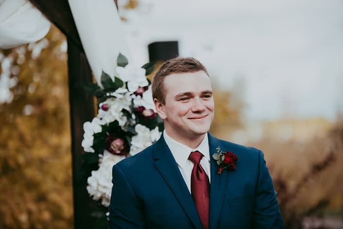 portrait of groom in navy suit with red spray rose boutonniere and red tie smiling in front of rustic archway