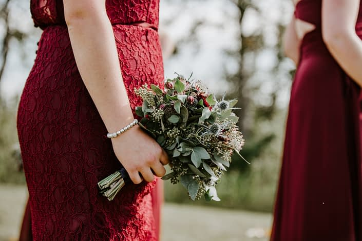 Bridesmaid wearing burgundy lace gown and holding a burgundy and blue bouquet with eucalyptus
