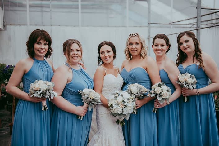 bride and bridesmaids in sky blue dresses with ivory and cream roses and grey dusty miller greenery