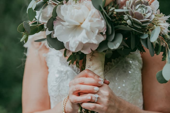 close up of bridal bouquet handle with blush penoy, lola blush succulent and silver dollar eucalyptus, handle is wrapped with ivory lace and brides rosary