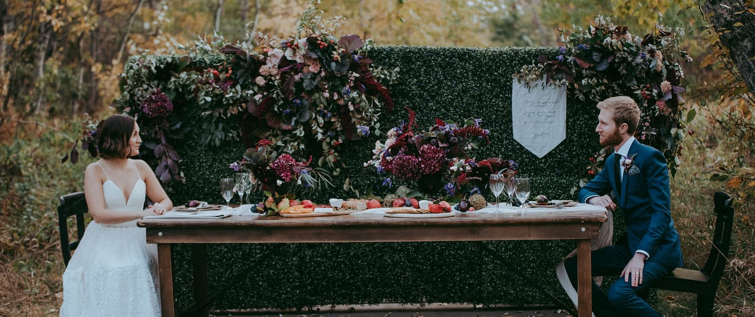 Styled shoot at McKenzie trails in Red Deer with bride and groom sitting at a tabe with a boxwood backdrop covered in autumn florals and charcuterie board