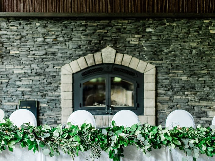 Head table in front of grand fireplace at Canyon Ski Resort with fresh greenery garland made of salal and eucalyptus.