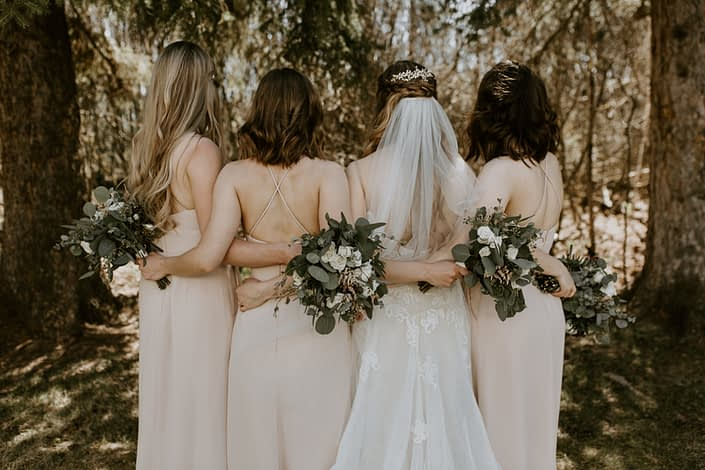 Bride and bridesmaids with blush, white & burgundy bouquets behind their backs