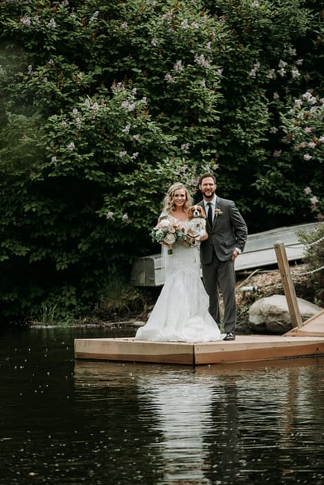 bride and groom on dock at pond holding spaniel puppy dog with bridal bouquet in white and blush and eucalyptus