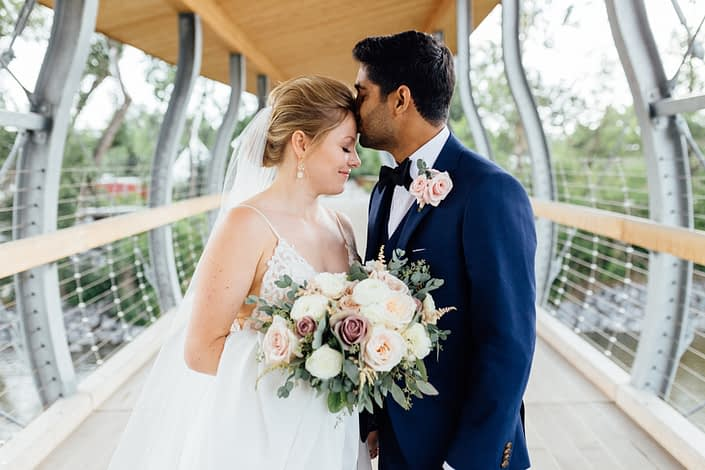 Jill and Jason; groom wearing blush pink boutonniere made of spray roses and eucalyptus; bride holding romantic blush bridal bouquet featuring white o'hara garden roses, quicksand roses, white ranunculus, and pale pink astilbe with eucalyptus greenery.