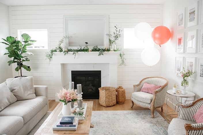 bridal shower decorations including balloons, vase of pale pink astilbe, and fresh greenery along fireplace mantle