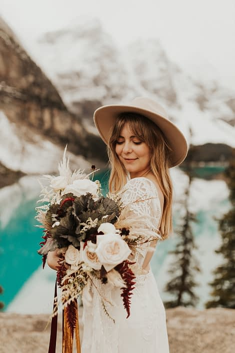 Moraine Lake Elopement Styled Shoot - model wearing ivory bridal gown and hat holding pampas grass bouquet with blush roses and pops of red tied with trailing ribbons.