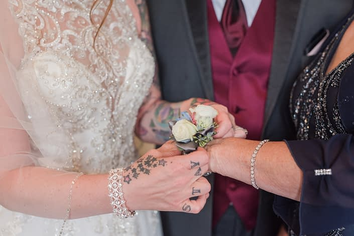 Bride putting on corsage for mother of the bride. It was designed with white spray roses, blue delphinium and pale pink astilbe with a touch of seeded eucalyptus on a grey pearl wristlet.