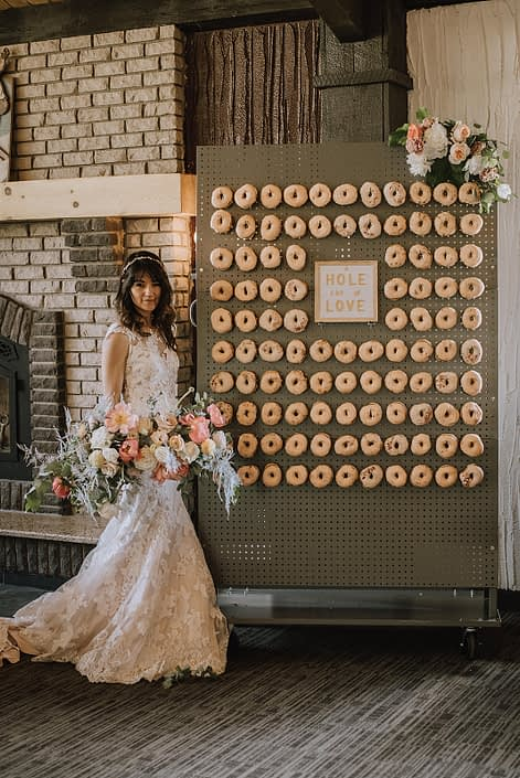 Bride holding a large blush and coral bouquet featuring coral charm peonies, roses, silver plumosa and greenery standing next to a doughnut wall with a floral arrangement attached to the top corner.