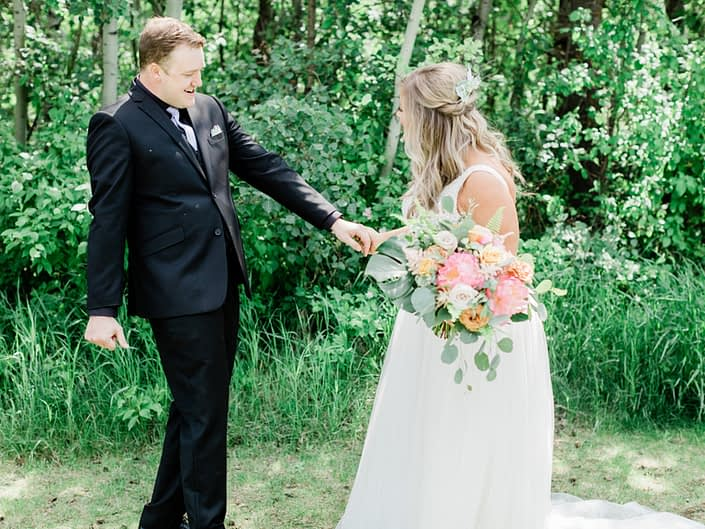 Griffin and Taylor holding coral charm peony bouquet with monstera leaves, boston fern, and eucalyptus.