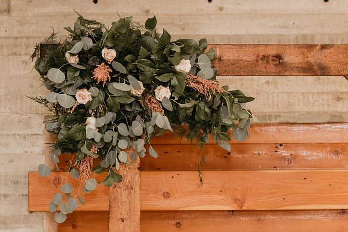 rustic wedding arch way with floral corner accent made with blush roses and pink astilbe and silver dollar eucalyptus