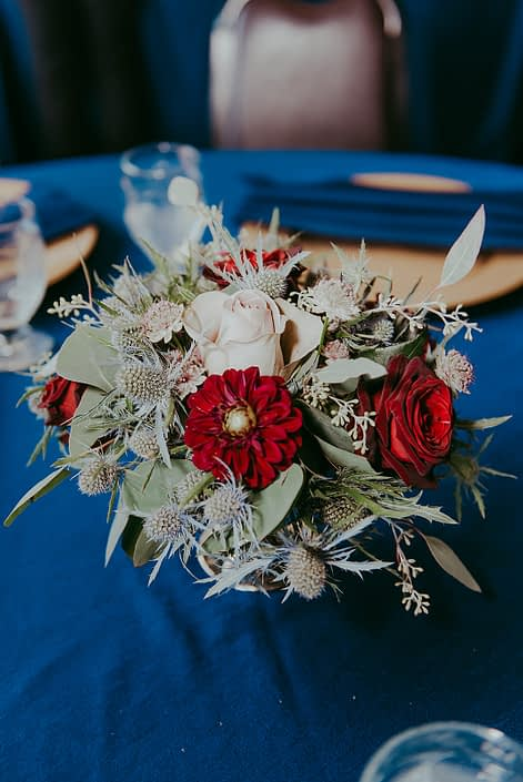 RCMP wedding centrepieces designed with burgundy dahlias, navy eryngium, black baccara roses and eucalyptus in compote vases