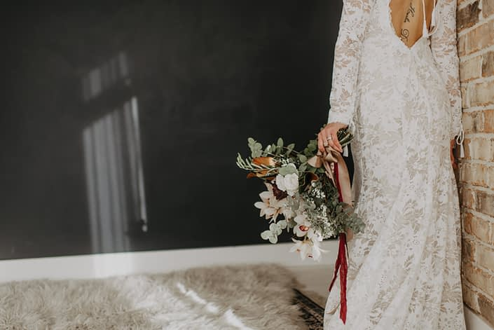 Neutrals Styled Shoot with Down the Aisle - Neutral coloured bridal bouquet with orchids, roses, magnolia leaves and eucalyptus greenery tied with trailing ribbons.