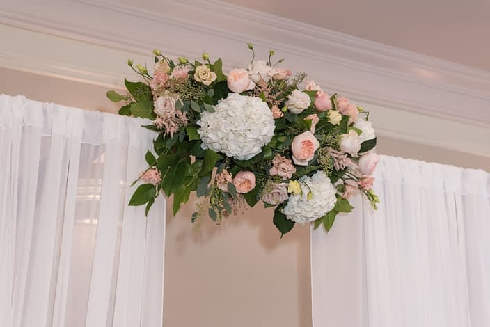 Rustic Pastel Wedding - Aisle archway arrangement for the ceremony made of white hydrangeas, Juliet garden roses, apricot lisianthus, astilbe, quicksand roses and salal and eucalyptus greenery.