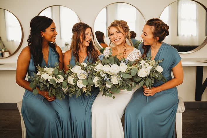 Bride and bridesmaids wearing dusty blue and holding bouquets designed with Tibet roses, white ranunculus, white astilbe, delphiniums, eryngium and eucalyptus.