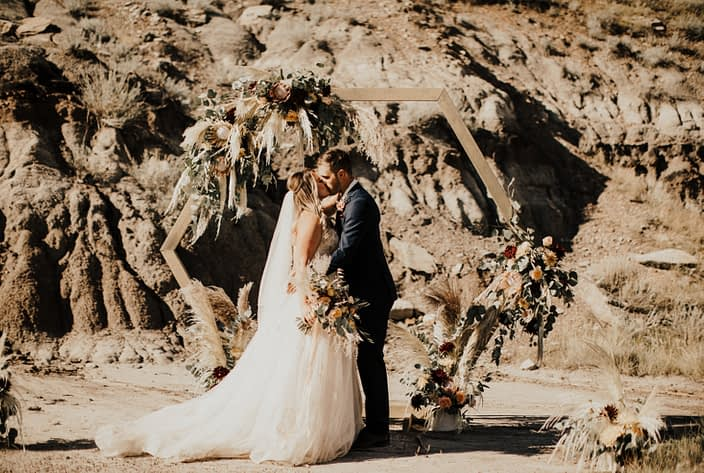 Bride and groom kissing in Drumheller desert with boho bridal bouquet