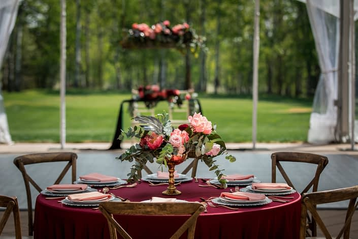 Gold compote centerpiece with black monstera leaves, coral charm peony, burgundy dahlia and cinerea eucalyptus ona burgundy tablecloth with vineyard chairs