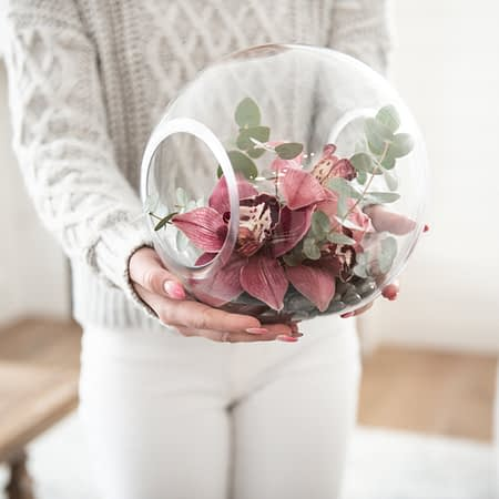 The Emma arrangement of cymbidium orchids and eucalyptus in a double opened glass globe