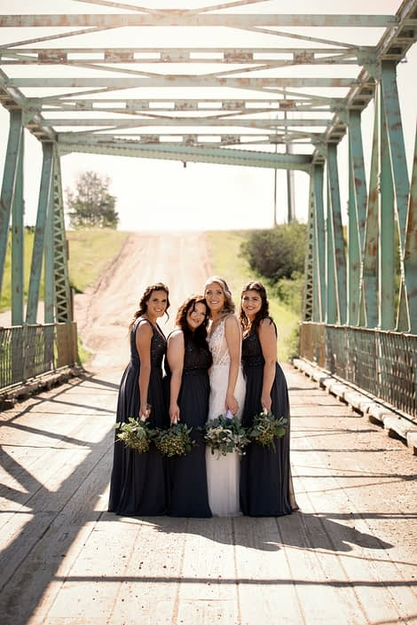 Bride with bridesmaids wearing blue dresses with white and blue bridal bouquet and greenery bridesmaids bouquets under a blue bridge