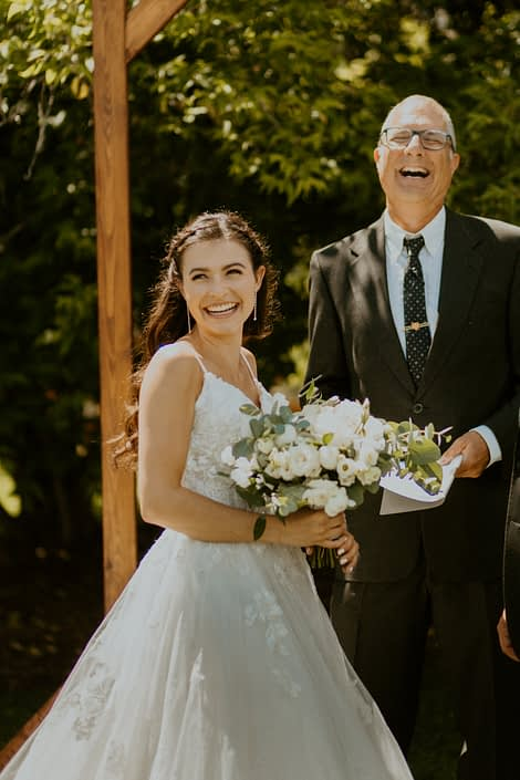 Outdoor ceremony; bride laughing with white bridal bouquet designed with lisianthus, ranunculus, Playa Blanca roses, spray roses, sweet peas, eucalyptus and Italian ruscus