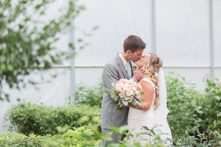 Megan and Steven kissing in a greenhouse. Megan is carrying a blush pink bridal bouquet made of Juliet garden roses, quicksand roses, apricot lisianthus, astilbe, Jana spray roses, dusty miller and eucalyptus.