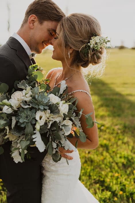 Leah and Chance; bride hair flowers made of white spray roses, lisianthus and astilbe with a touch of grey toned greenery; bridal bouquet with a vintage feel designed with white playa blanca roses, lisianthus, astilbe, Blue Star succulents, dusty miller and eucalyptus.