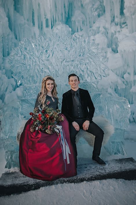 Ice castels engagement photos with a bridal bouquet of tulips, burgundy frittilaria and skimmia and trailing grey silk ribbons