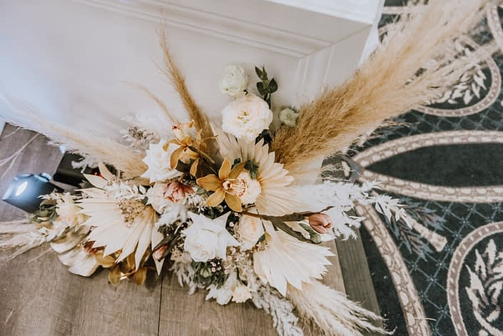 Arrangement made of orchids, pampas grass, white playa blanca roses, and dried leaves and branches.