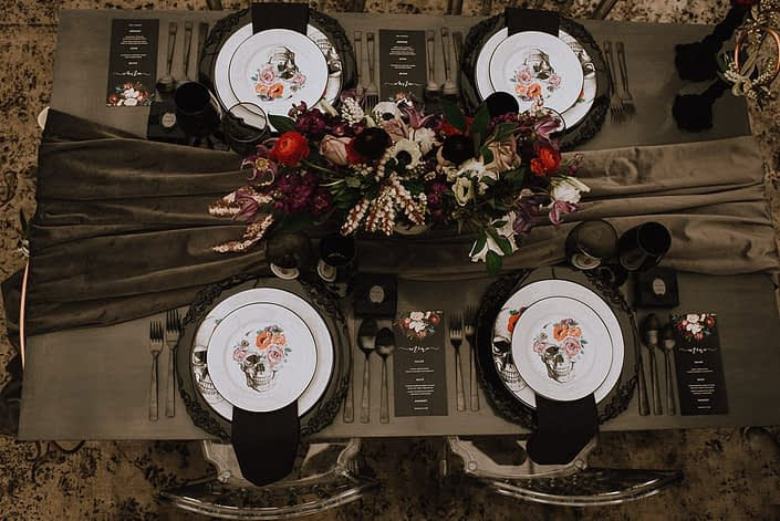 alternative wedding table setting with flower skull plates and black chargers and grey velvet table runner and centerpiece with red ranunculus and white anemone and amnesia roses and purple clematis and white lisianthus and white pieris