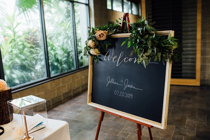 """Jill and Jason's Romantic Blush Calgary Zoo Wedding """"welcome"""" sign decorated with a thin fresh greenery garland accented with quicksand roses."""