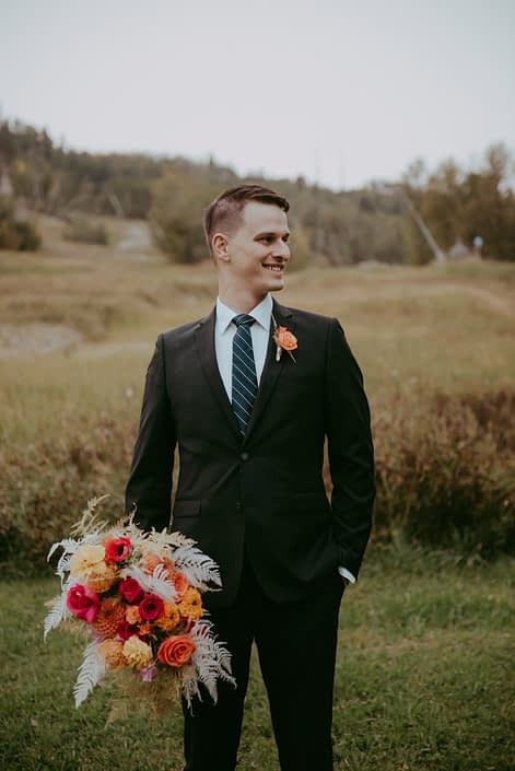 Groom with colourful fuchsia and orange bridal bouquet and boutonniere