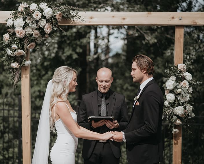 Bride and groom under floral covered archway at outdoor ceremony