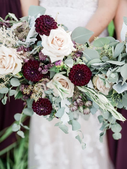 Burgundy country chic bridal bouquet designed with burgundy astrantia, astilbe, burgundy dahlias, brown lisianthus, quicksand roses, dusty miller, olive branches and various types of eucalyptus.