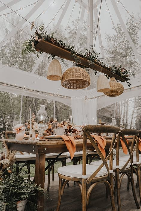 Modern boho tablescape decorated with natural elements and terracotta tones such as woven baskets, greenery, ceramics, pottery and wood with flowers