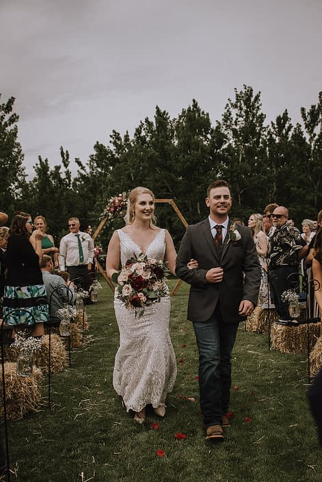 Bride and groom walking from ceremony holding rustic red and blush bridal bouquet featuring red charm peonies, quicksand roses, blush spray roses, burgundy astrantia, light pink astilbe and eucalyptus greenery.