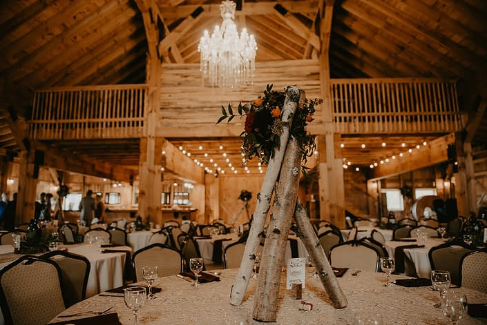 Teepee centrepiece for Hayley and James' rustic fall wedding designed with burgundy dahlias, hearts garden roses, orange spray roses and solidago with seeded eucalyptus and italian ruscus greenery atop a teepee of birch poles.