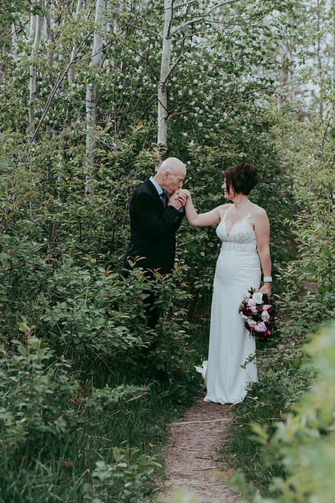 Groom kissing bride's hand while she is holding a pink and burgundy bridal bouquet made with helleborus, peonies, ranunculus, black bacarra roses, plum scabiosa, tulips, astrantia and eucalyptus.